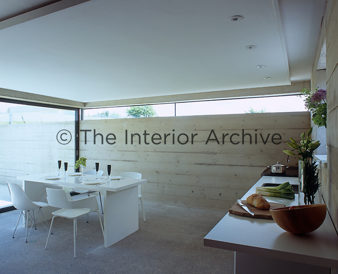 The concrete kitchen diner is furnished with a contemporary white table and a selection of designer chairs
