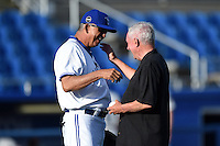 Florida State League President Ken Carson hugs Omar Malave (29) after throwing out the ceremonial first pitch before a game between the Clearwater Threshers and Dunedin Blue Jays on April 10, 2015 at Florida Auto Exchange Stadium in Dunedin, Florida.  Clearwater defeated Dunedin 2-0.  (Mike Janes/Four Seam Images)