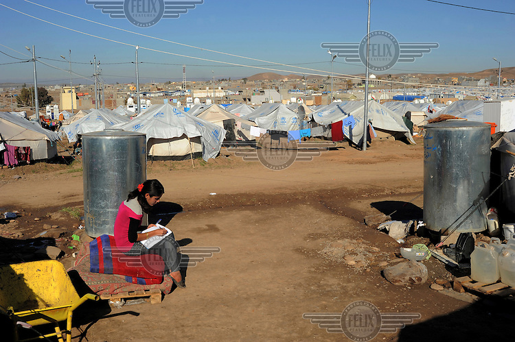 Avat, a student, writing out her English homework in a textbook at the Kawergosk Syrian Refugee Camp.
