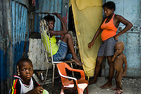 A Haitian family in front of the shack in the slum of Cité Soleil, Port-au-Prince, Haiti, 24 July 2008. Cité Soleil is considered one of the worst slums in the Americas, most of its 300.000 residents live in extreme poverty. Children and single mothers predominate in the population. Social and living conditions in the slum are a human tragedy. There is no running water, no sewers and no electricity. Public services virtually do not exist - there are no stores, no hospitals or schools, no urban infrastructure. In spite of this fact, a rent must be payed even in all shacks made from rusty metal sheets. Infectious diseases are widely spread as garbage disposal does not exist in Cité Soleil. Violence is common, armed gangs operate throughout the slum.