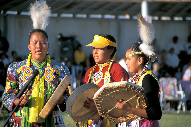 Group of teenage girls dressed in traditional regalia play hand drums and sing traditional songs during the Blackfeet Indian Days Festival, Browning Montana
