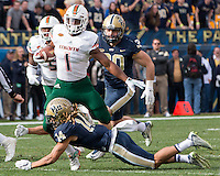 Pitt defensive back Avonte Maddox (14) tackles Miami running back Mark Walton (1). The Miami Hurricanes football team defeated the Pitt Panthers 29-24 on  Friday, November 27, 2015 at Heinz Field, Pittsburgh, Pennsylvania.