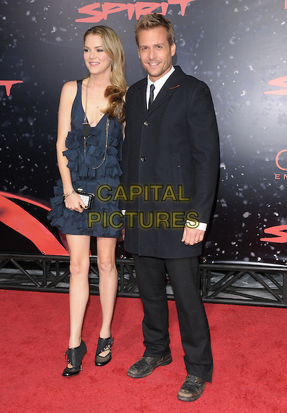"JACINDA BARRETT & GABRIEL MACHT.The Lionsgate L.A. Premiere of ""The Spirit"" held at ChineseTheatre in Hollywood, California, USA..December 17th, 2008.full length black suit blue ruffled ruffles dress clutch bag married husband wife.CAP/DVS.©Debbie VanStory/Capital Pictures."