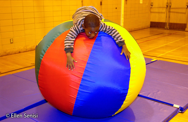 MR / Schenectady, NY                                  .Yates Arts-in-Education Magnet School (urban school)..Pre-Kindergarten class; NYS Universal Pre-K Program..Boy (4, African-American) balances self and holds on to big ball on mat in gym class after being placed there by gym teacher...Far2..©Ellen B. Senisi
