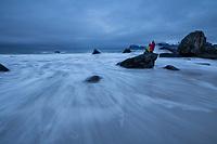 Female traveler takes photo of wild sea from tidal rock at Myrland beach, Flakstadøy, Lofoten Islands, Norway