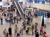 People walking through Grand shopping hall Schiropl airport Amsterdam Holland