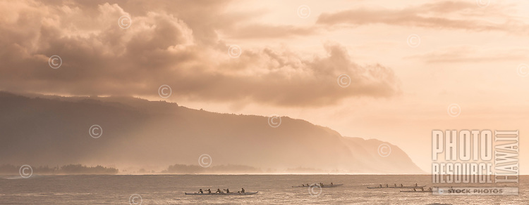 Canoe paddlers at sunset in Haleiwa, with Ka'ena Point in the background, O'ahu.