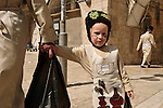 Israel, Jerusalem. Ultra Orthodox Jewish boy with his father in costumes on Purim holiday at in the Me?a She?arim quarter, the father is carrying ?Mishlo?ach Mnot? (Purim gifts)<br />