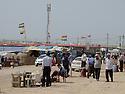 Iraq 2013 .The entrance of Domiz Refugee Camp with Kurdish flags, money changers, cars... .Irak 2013 .L'entree du camp de refugies de Domiz avec petits commerces, changeurs d'argent, voitures et  drapeaux kurdes flottant au vent.