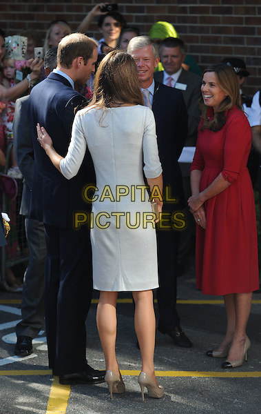 The Duke and Duchess of Cambridge's .visit to the Royal Marsden Hospital, Sutton, Surrey, England .Thursday 29th September 2011.Prince William Kate Catherine Middleton full length royals royalty white dress hand on back behind rear grey gray blue suit married husband wife.CAP/CAS.©Bob Cass/Capital Pictures.