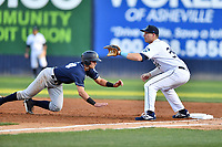 Asheville Tourists first baseman Grant Lavigne (34) awaits the pickoff throw as Max Burt (24) dives back to first base during a game against the Charleston RiverDogs at McCormick Field on April 10, 2019 in Asheville, North Carolina. The  RiverDogs defeated the Tourists 5-3. (Tony Farlow/Four Seam Images)
