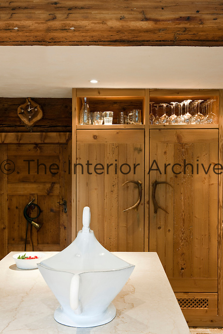 A wood-panelled cupboard with handles made of antlers disguises a double fridge in the kitchen