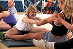 young women working together during aerobic stretching  exercise in health club studio