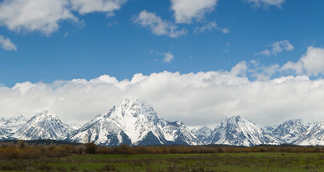 The Grand Teton Mountains covered in snow with a blue ski and clouds seen from a pullout in Grand Teton National Park, June 2, 2011.  Photo by Gus Curtis