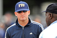 11 February 2012:  FIU Head Coach Jake Schumann speaks with the umpire prior to the start of the game.  The University of Massachusetts Minutewomen defeated the FIU Golden Panthers, 3-1, as part of the COMBAT Classic Tournament at the FIU Softball Complex in Miami, Florida.