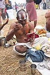Indian Men applying face paint after holy bath in the Ganges River in Allahabad for Kumbh Mela Festival.