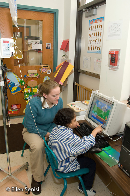 MR / Albany, NY.Langan School at Center for Disability Services .Ungraded private school which serves individuals with multiple disabilities.Child (boy, 7, African-American,  Pierre Robin Syndrome) uses a computer with letter recognition software while given food through a gastric tube feeding while the teacher supervises. Child is pointing to computer screen as he is using a touch screen selection method...MR: Ris4; Smi24.© Ellen B. Senisi
