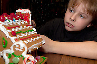 Boy age 10 decorating Christmas gingerbread house. St Paul Minnesota USA