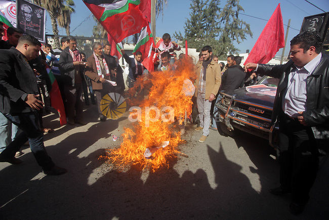 Palestinian protesters burn French flag, during a protest outside the French Cultural Center calling for the release of Lebanese militant Georges Ibrahim Abdallah (portrait L) and Ahmed Saadat, leader PFLP (portrait R), in Gaza City on January 21, 2013. Photo by Ashraf Amra
