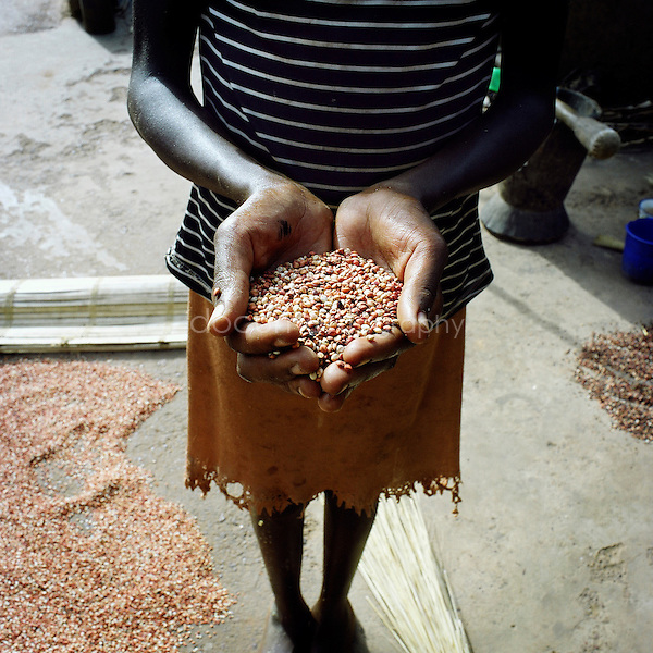 A young girl holding some millet in her hand.