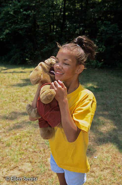 MR / Guilderland, NY.Westmere Elementary Public School playground.BOCES Deaf and Hard-of-Hearing (HOH) class .Girl (12, African-American, Fetal Alcohol Syndrome, Hard of Hearing, well-cared for in adoptive family) hugs stuffed animal..MR: Sta3.film scan; PN#: 30567; FC#: 21624-00115.©Ellen B. Senisi