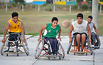 Alejandro Jarquin (center) chases the basketball while pushing his wheelchair forward during practice in Zipolite, a town in Oaxaca, Mexico. Jarquin and the other players are part of the Oaxaca Costa wheelchair basketball team.