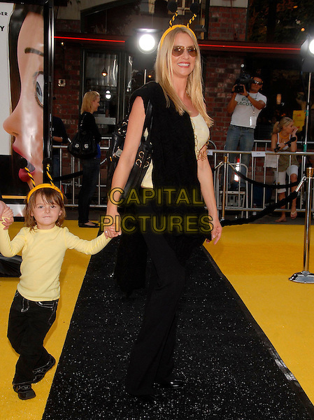 """NICOLLETTE SHERIDAN & guest.attends The Paramount Picture L.A. Premiere of """"Bee Movie"""" held at The Mann's Village theatre in Westwood,  L.A. California, USA,  October 28 2007.                                                                      full length Nicolette sunglasses yellow vest top gold necklace black holding hands kid child.CAP/DVS.©Debbie VanStory/Capital Pictures"""
