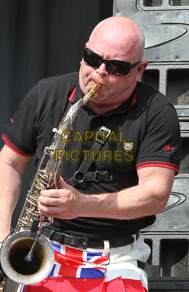 Madness .V Festival 2012 - Day Two, Hylands Park, Chelmsford, Essex, England..August 19th 2012.on stage in concert live gig performance music half length black top kilt union jacket red white blue sax saxophone sunglasses shades   .CAP/JIL.©Jill Mayhew/Capital Pictures