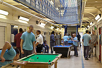 Prisoners play pool and socialise during a recreation period on C wing at the Young Offenders Institution, Aylesbury, United Kingdom.
