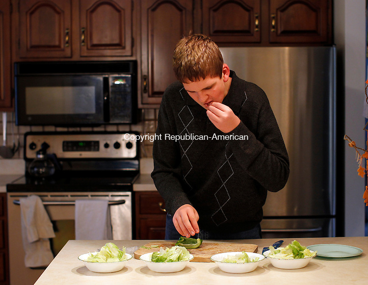Barkhamsted CT- 22, October 2010-102210CM08  Erik Lambert tastes a piece of lettuce as he helps prepare dinner in his families kitchen in Barkhamsted.  Lambert, who is Autistic has been receiving special help which enables him to lead a productive and independent life. Christopher Massa Republican-American