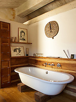 The bathroom features a contemporary roll-top bath in a rustic setting