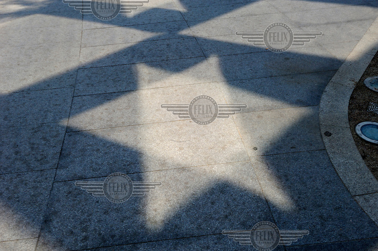 Relected light from London's Swiss Re building forms a star on the pavement. The building, designed by British architect Sir Norman Foster, is colloquially known as 'the Gerkin', and officially as 30 St Mary Axe.