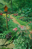 Shady summer garden with path and handmade cedar birdhouse Missouri United States America USA
