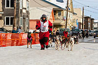 Rookie musher Jane Faulkner runs in front of her dogs into the finish chute in Nome during the 2010 Iditarod