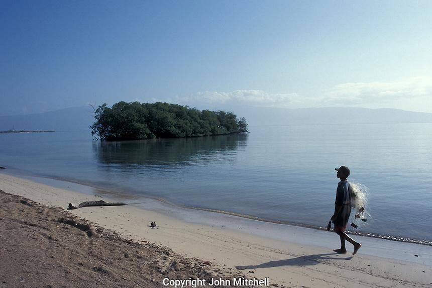 Boy walking along a beach in Barahona, Dominican Republic
