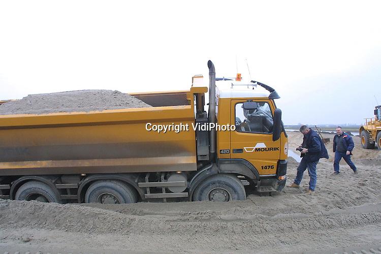 Foto: VidiPhoto..ECHTELD - Zandauto's rijden bij Echteld af en aan om een zandlichaam te maken voor de Betuwelijn. Niet altijd gaat dat goed. Dinsdag zakte een van de zandauto's tot aan zijn assen weg tijdens de aanleg van een zanddam. Om het zwaarbeladen voertuig los te kunnen krijgen moest er eerst een nieuwe zanddam gebouwd worden naast de weggezakte wagen. Vervolgens werd de bak met een graafmachine leeggehaald.  Pas daarna kon een shovel de wagen weer los trekken.