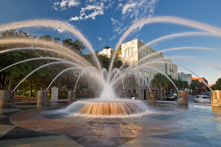 """I have many photos of this fountain in Charleston SC . But I always feel like I never really """"got it"""", until now. I really like this photo of the fountain that is in Waterfront Park in Charleston SC. The sunlight lighting the water streams, and some Charleston architecture behind it. To the left, the tree covered walkway through Battery  park, (with the sun peeking through) that leads to the famous Pineapple Fountain. Have a look at the rest of this Charleston stock photo gallery."""