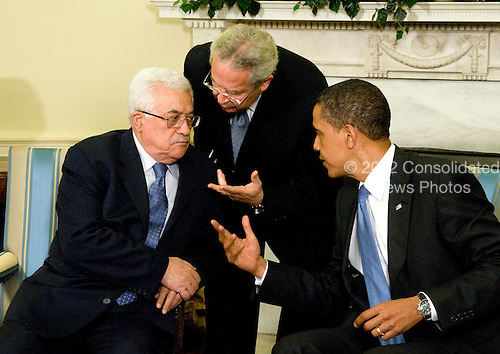 Washington, D.C. - May 28, 2009 -- United States President Barack Obama, right, through interpreter Gamal Helal, center, makes a point to President Mahmoud Abbas (Abu Mazen) of the Palestinian National Authority, during a photo-op in the Oval Office of the White House on Thursday, May 28, 2009..Credit: Ron Sachs / CNP