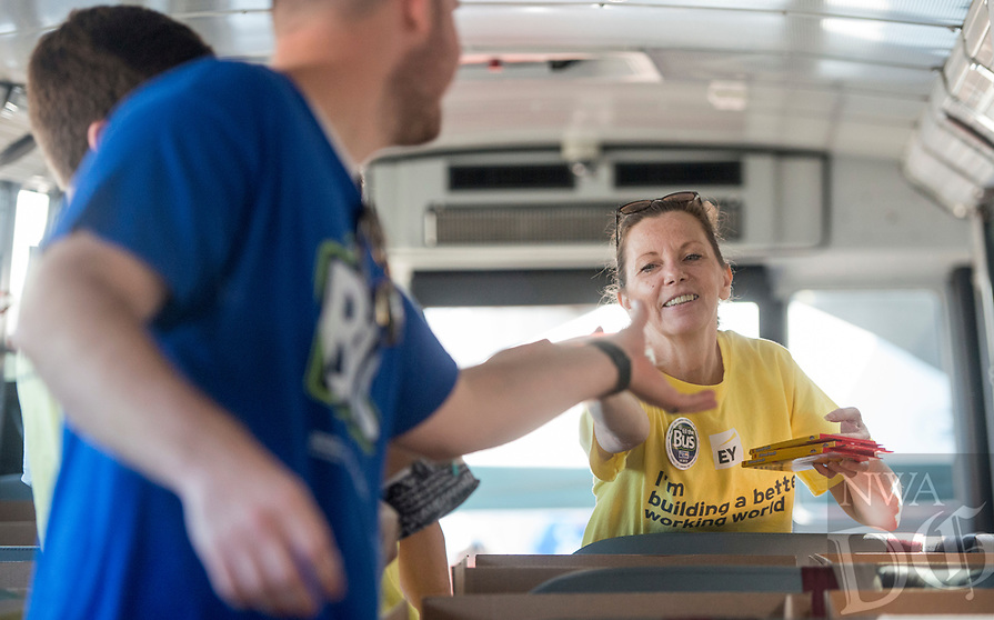 NWA Democrat-Gazette/BEN GOFF @NWABENGOFF<br /> Donna Prince hands supplies to Johnathan Loessel while volunteering with other employees from Ernst & Young in Rogers Friday, Aug. 3, 2018, at the United Way of Northwest Arkansas Fill the Bus drop-off location at the Walmart Supercenter on Pleasant Crossing Boulevard in Rogers. Volunteers are manning busses at ten Walmart Supercenter locations in Northwest Arkansas and Pineville, Mo. from 9:00 a.m. to 3:30 p.m. Friday and Saturday to sort donated school supplies. The donations will go directly to the district the Walmart location is in. Over the past ten years, the annual drive has helped more than 35,000 students in 12 school districts get the supplies they need to start the school year.