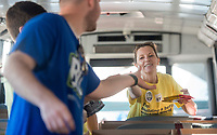 NWA Democrat-Gazette/BEN GOFF @NWABENGOFF<br /> Donna Prince hands supplies to Johnathan Loessel while volunteering with other employees from Ernst &amp; Young in Rogers Friday, Aug. 3, 2018, at the United Way of Northwest Arkansas Fill the Bus drop-off location at the Walmart Supercenter on Pleasant Crossing Boulevard in Rogers. Volunteers are manning busses at ten Walmart Supercenter locations in Northwest Arkansas and Pineville, Mo. from 9:00 a.m. to 3:30 p.m. Friday and Saturday to sort donated school supplies. The donations will go directly to the district the Walmart location is in. Over the past ten years, the annual drive has helped more than 35,000 students in 12 school districts get the supplies they need to start the school year.