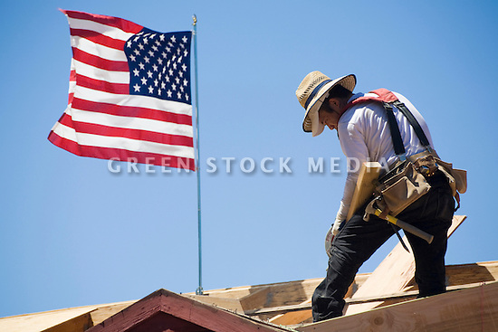 A construction worker beside an American flag working on a roof of a single family home construction site. Los Altos, California, USA