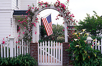 USA, California, Mendocino, gate to house with roses framing a US flag