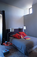 Coloured cushions on the bed and a flower-shaped  side table add a splash of colour to this pale grey bedroom