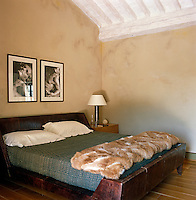 The bed in the main bedroom has a green Indian silk cover and the walls are decorated with black and white photographs by Fiorenzo Niccoli