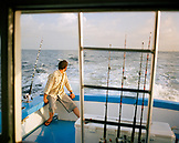 USA, Florida, man sitting on fishing boat heading out to sea, Destin