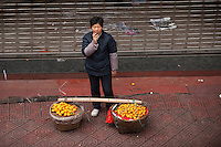 A Woman Standing With Fruit In Baskets In Chongqing, China.  © LAN
