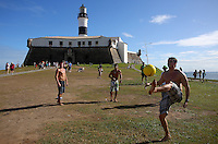 People play football in front of the Forte de Santo Antonio da Barra in Salvador, Brazil, one of the 12 host cities of the 2014 FIFA World Cup