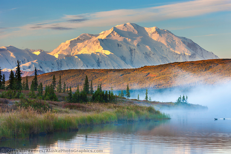 Morning fog over the calm waters of Wonder Lake at sunrise, Denali looms in the distance, Denali National Park, Alaska.