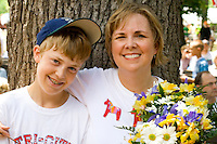 Mom holding bouquet and son enjoy festivities. Svenskarnas Dag Swedish Heritage Day Minnehaha Park Minneapolis Minnesota USA