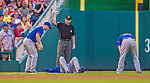 26 July 2013: New York Mets infielder Justin Turner lies flat on his back after catching a fly ball and colliding with outfielder Andrew Brown, as David Wright looks on and umpire David Rackley signals the out during a game against the Washington Nationals at Nationals Park in Washington, DC. The Nationals bounced back from their loss in the first game of their day/night doubleheader, with a 2-1 nightcap win. Mandatory Credit: Ed Wolfstein Photo *** RAW (NEF) Image File Available ***